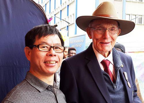 图6:前议员弗兰克在游行期间遇见老朋友法轮功学员约翰(John Zhuo)