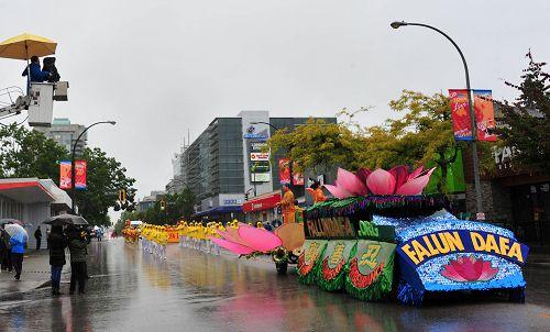 图4:电视台和观众冒雨拍摄法轮功学员游行队伍。