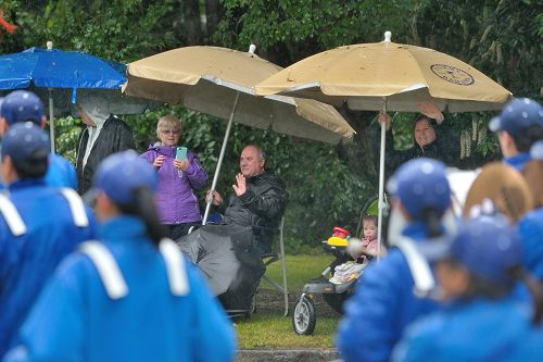 图6:市民冒雨观看游行,向法轮功学员游行队伍挥手致意。