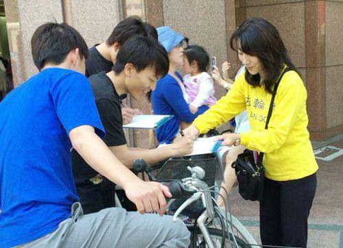 图1-2:日本法轮功学员在福冈天神征集声援起诉迫害元凶江泽民的签名。许多民众签名后,并对法轮功学员说:我们支持你们。