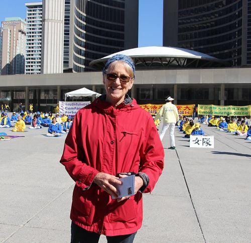 圖6:多倫多居民Adriana Reasner和先生一起觀看了很久法輪功學員的集體煉功。她表示這個功法讓人很平靜。