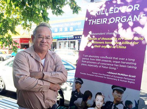 图5:马来西亚华人邢先生(Mr Heng)站在法轮功学员真相横幅前面感慨表示:希望让更多人了解中共非法迫害法轮功学员的罪行。