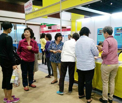 图6:二零一六年泰国健康博览会上,人们来法轮功展位了解功法。