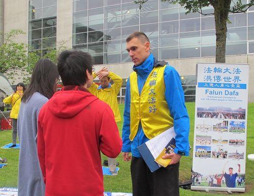 图1-2:法轮功学员在苏格兰格拉斯哥西部艺术节上向游客讲真相