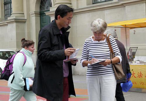 图1-3:路人在伯尔尼火车站广场了解法轮功真相并签名制止中共活摘器官。