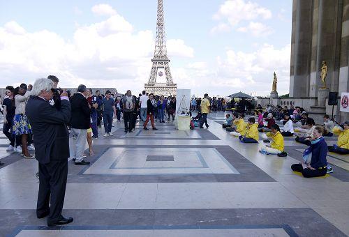 图1-3:二零一六年六月二十六日下午,法轮功学员在巴黎艾菲尔铁塔下的人权广场上传播真相。图为法轮功学员祥和的功法场面和真相展板都吸引了中西游客的目光。
