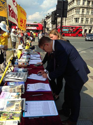 图9:二零一六年七月二十日,英国名演员伊恩哈特爵士(Sir Ian Hart)从马路对面走来对法轮功学员表示支持,并签名反迫害