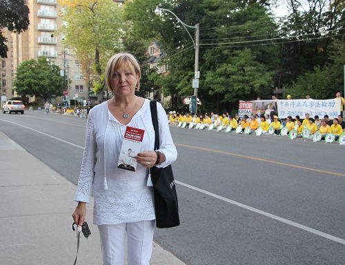图13:住在中领馆附近的居民Marianne在烛光悼念现场看了很久,她呼吁要加拿大和美国政府都要站出来制止这场迫害。