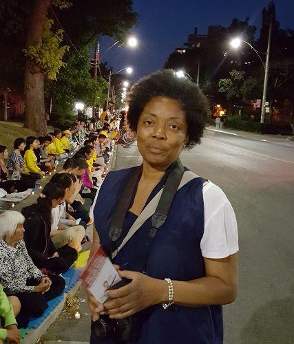 """图15:多伦多居民Lana骑车经过现场,她停下了拍了很多照,她说:""""我要网上签名,向我们的总理请愿,人们不应该因为信仰受到迫害。"""""""