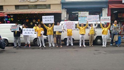 '图5:在圣保罗华人商业街(Liberdade)上游行的活动,学员打着横幅,举着展板,呼吁中共停止迫害法轮功'