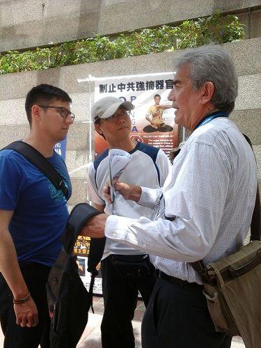 """图2:香港法轮功学员在""""国际器官移植协会""""设置流动真相点,向来往行人讲真相。"""