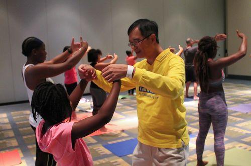 '图1-4:瑜伽展览会上法轮功功法学习厅内,人们正在学炼法轮功功法。'