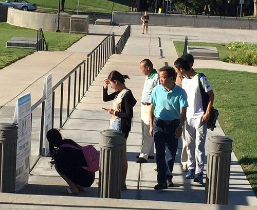 图5:游客观看犹他州议会大厦门口的法轮功真相展板