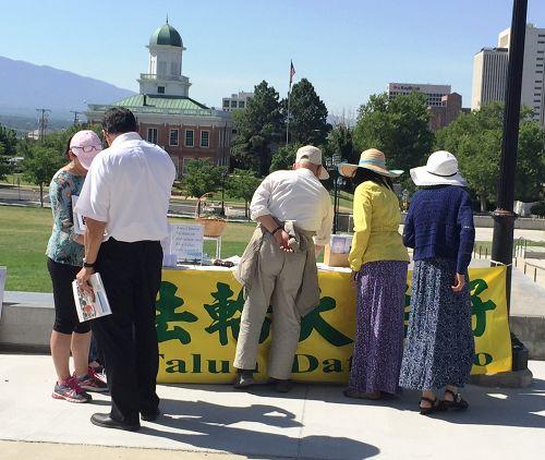 图6:华人游客到犹他州议会大厦门口的法轮功真相展位取资料