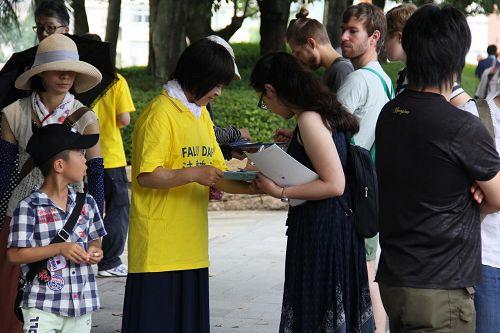 '图1-2:日本法轮功学员在广岛核爆七十一周年日来到广岛和平公园,向来自世界各地的民众揭露中共活摘法轮功学员器官的罪行,并征集签名声援诉江。'