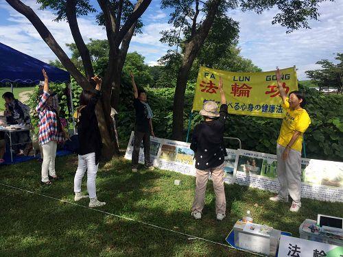 图1-2:在稻泽夏季活动节展位上学炼法轮功的市民们