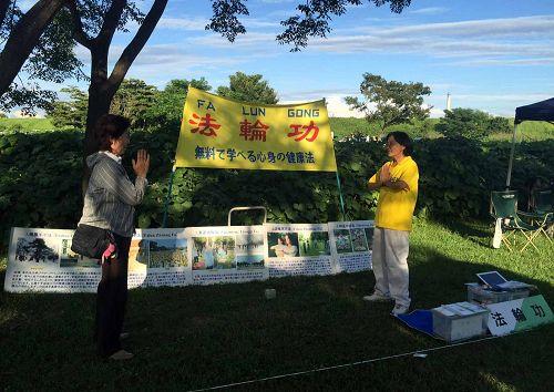 图3:后藤女士(左)在稻泽夏季活动节展位上当场学炼法轮功