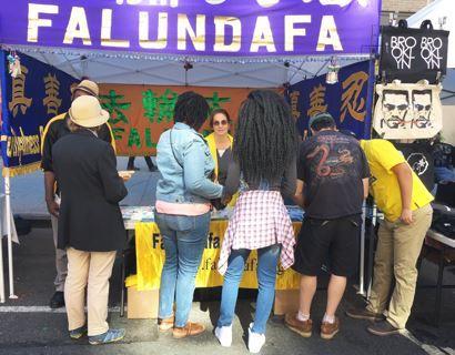 '图4:法轮功学员在纽约布鲁克林一年一度的周末集市上设立展位,向民众传播法轮功的真相。许多民众驻足了解大法真相。'