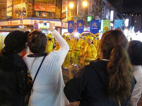 图4:民众与游客纷纷拍摄法轮功学员组成的闪亮队伍。