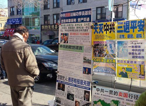 '图1~3:大年初二,法轮功学员们在热闹的布碌仑街上向民众传递真相,很多华人民众驻足阅读真相展板'
