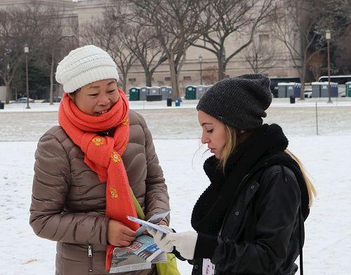 '图01:二零一七年一月七日下午,华府法轮功学员李女士在美国国家广场向过往游客传递真相。'