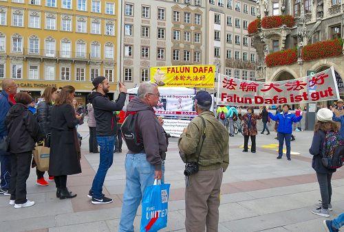 '图1:法轮功学员在玛琳广场展示功法及揭露中共活摘器官的横幅吸引了民众观看。'
