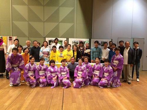 '图1:稻泽市民会馆的六鹿(Mr.Mutsuga)馆长与部份参加本次活动的团体人员法轮功展位前合影留念。'