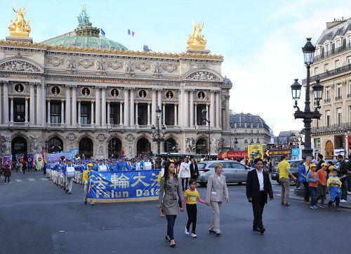 '图3:奥斯塔丽女士全程参加了法轮功学员的集会与游行,并一直走在游行队伍的最前面。图为游行队伍经过巴黎歌剧院(OpéraGarnier)。'