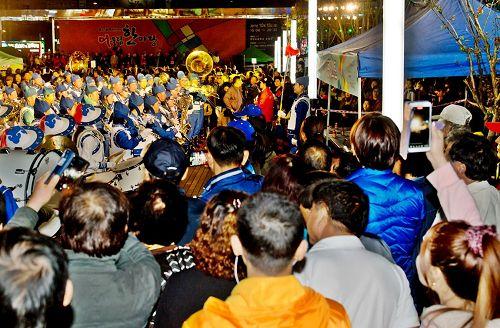 '图5:天国乐团和法轮功功法演示队面向审查团和观众进行表演,观众纷纷拿出手机拍照、录像。'