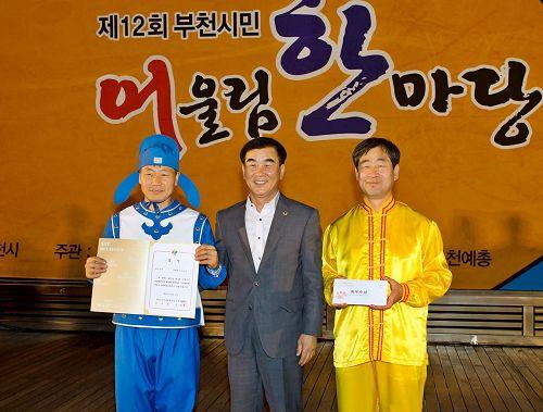 '图6:韩国京畿道议会文化观光委员长(中)给参加本次庆典活动获一等奖——最优秀奖的法轮功团体颁奖。'