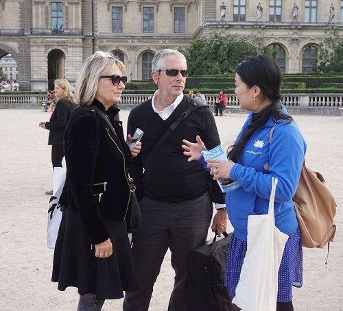 '图4:游行在卢浮宫广场结束后,这对夫妇仍在向法轮功学员询问真相。'
