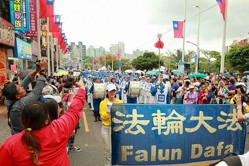 '图1:十月七日新北市举办淡水环境艺术节踩街活动,台湾法轮大法队伍最受瞩目,吸引数万民众驻足观看,并纷纷拿出手机拍照留影。'