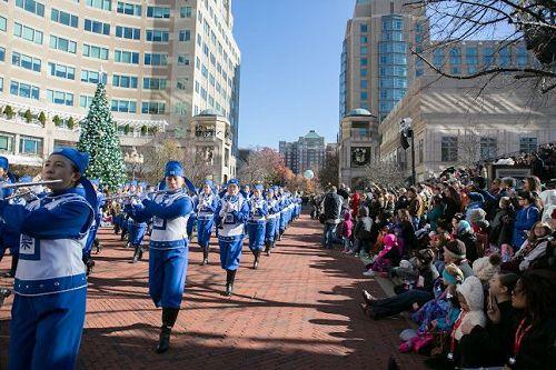 """'图1~5:二零一七年十一月二十四日,美国弗吉尼亚州瑞思顿(Reston)镇举办节日游行,有约一百五十名法轮功学员组成的天国乐团首次参加。游行主办方表示感谢,两旁观众欢迎。维州瑞斯顿市民SarahHappel说:""""他们的服装、帽子,一切都那么好,音乐也很动听。真是非常棒﹗""""'"""
