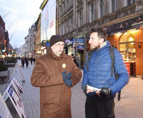 图8:Maciej Kędelski先生(右)认真听法轮功学员讲真相,手拿多张法轮功传单要送给亲朋好友