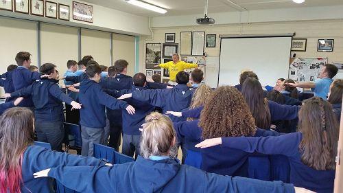 '图1~2:爱尔兰都柏林一所中学近日再次邀请法轮功学员来教授功法,图为该校即将参加高考的六年级学生们学炼法轮功功法动作'
