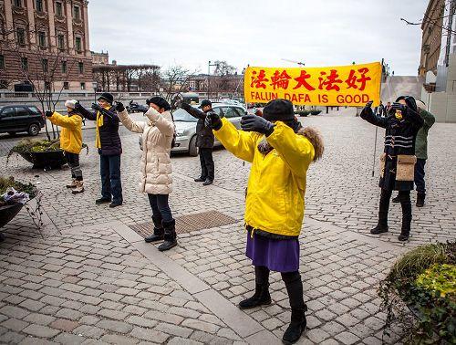'图1,瑞典法轮功学员在钱币广场上举办法轮大法信息日活动'