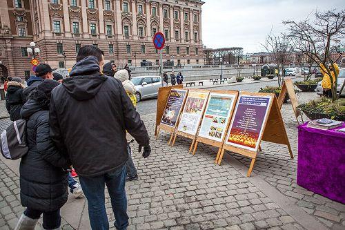'图2,在斯德哥尔摩最热闹的皇宫旁的钱币广场上,民众观看展板,了解法轮功真相。'