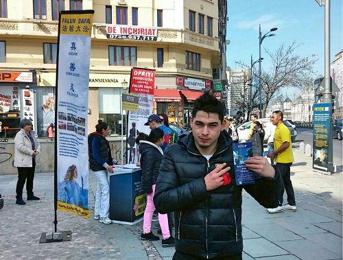 '图4:图中这位年轻人曾在中国呆了九年,他在征签表上签名后,手中拿着法轮功的真相传单表示,他支持法轮功学员反迫害。'