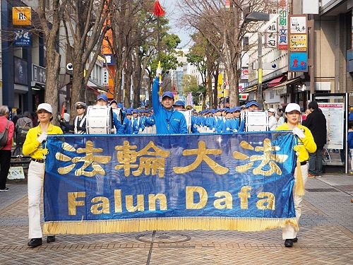 '图1:三月十九日,来自日本各地的法轮功学员齐聚横滨举行了游行活动,图为游行队伍经过横滨中心部的关内的场景'