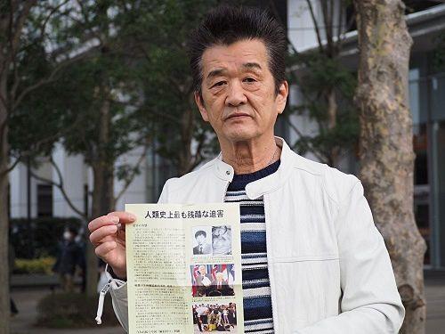 '图4:日本民众小高先生手持法轮功真相报纸表示期待和平'