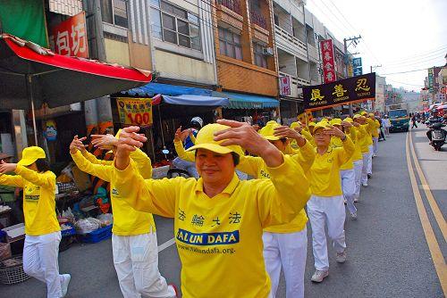 图2:法轮功学员在校庆踩街中表演法轮功功法。
