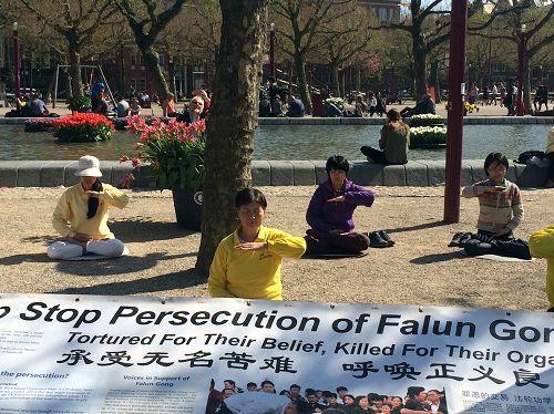 图1-2:荷兰部分法轮功学员在博物馆前的广场上举行了弘扬法轮<span class='voca' kid='53'>大法</span>活动,图为学员们集体打坐