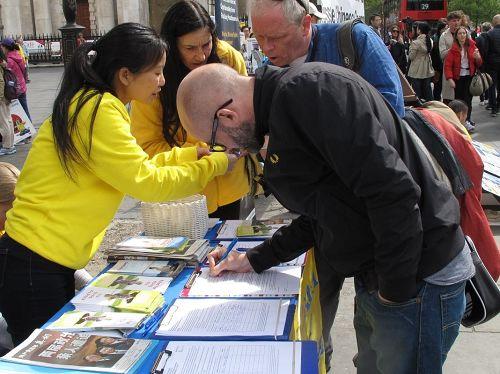 '图6~7::二零一七年四月二十二日,英国法轮功学员反迫害游行结束后在圣马丁广场(St.MartinPlace)展示真相、征签反迫害'