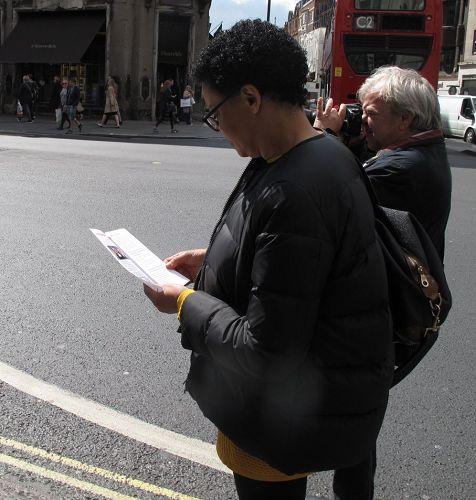 '图15:二零一七年四月二十二日,喜欢打坐的英国女士卡罗尔在伦敦摄政大街巧遇法轮功,感受到法轮功队伍发出的平和能量'