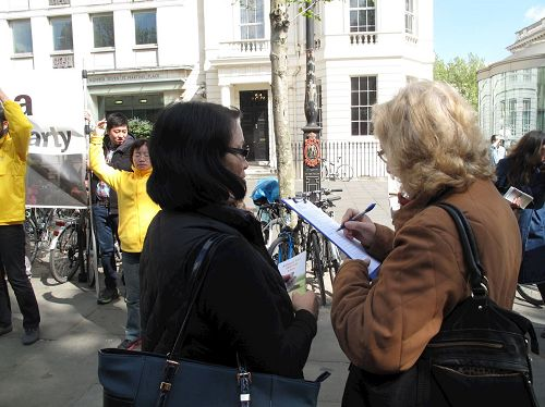 '图16:二零一七年四月二十二日,退休教师约翰逊女士在圣马丁广场被法轮功学员的平和抗议所吸引,了解真相后签名反迫害'