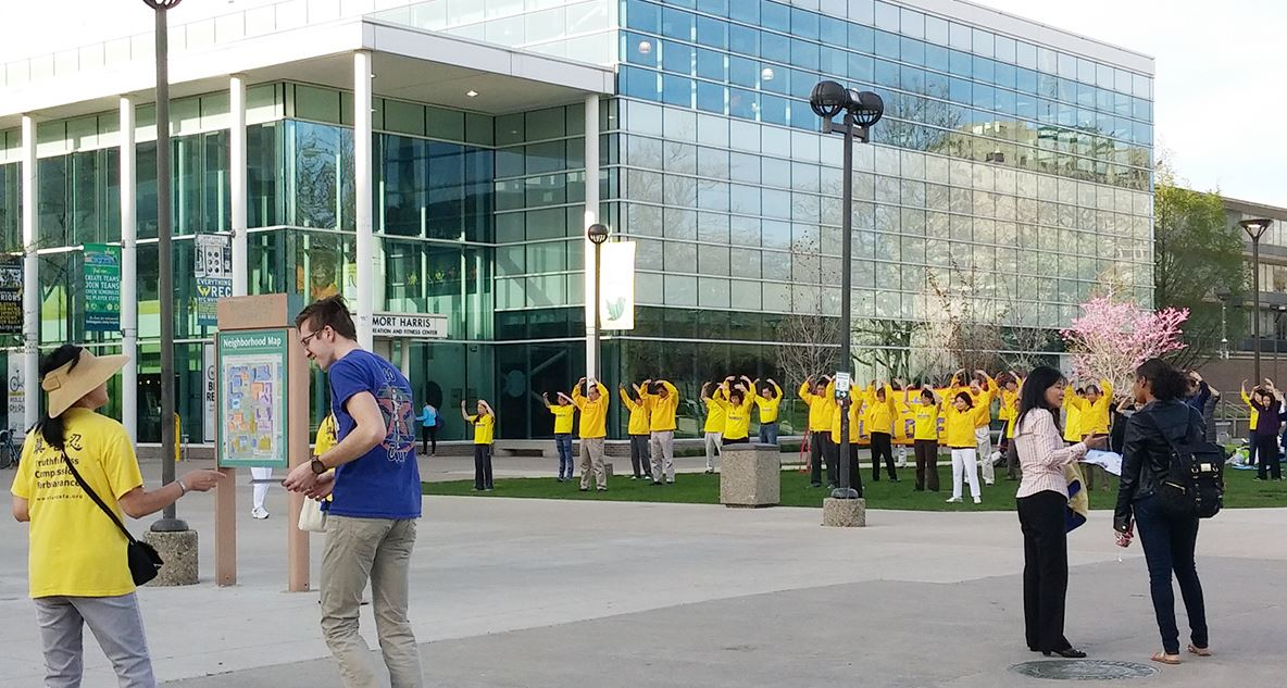 """4月25日,美国密歇根州部分法轮功学员们在底特律市内的韦恩州立大学校园(Wayne State University)以集体炼功和发法轮功真相资料的方式纪念""""四二五""""18周年 。(明慧网)"""