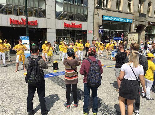 '圖4:在捷克布拉格市中心,路人駐足觀看法輪功學員演示功法'