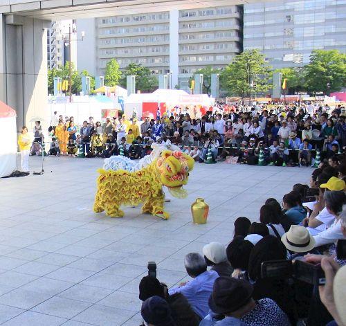 '图4~7:在演出广场进行表演的天国乐团、打腰鼓、狮子舞和法轮功五套功法演示,吸引了很多观众(图)'