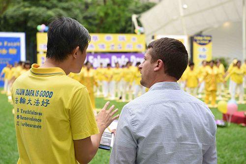 '图6:二零一七年五月二日,新加坡法轮功学员在芳邻公园庆祝即将来临的世界法轮大法日,路人驻足了解真相。'
