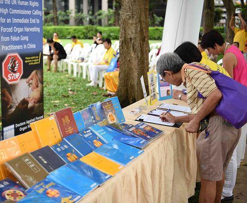 '图7~9:二零一七年五月二日,新加坡法轮功学员在芳邻公园庆祝即将来临的世界法轮大法日。图为各族裔民众了解真相后签名支持法轮功学员反迫害。'